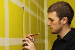 Uomo che misura parete interna fotografia stock libera da diritti
