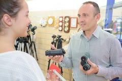 Uomo che mostra a cliente due binocoli di paia Fotografia Stock