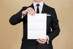 Uomo che mostra il libretto nero in bianco dell'opuscolo dell'aletta di filatoio Presenta dell'opuscolo Immagini Stock