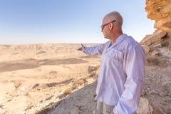Uomo che mostra indicando il paesaggio dei moutains del cratere del deserto Fotografia Stock