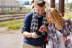 Uomo che mostra le maschere della donna sulla macchina fotografica digitale Fotografia Stock