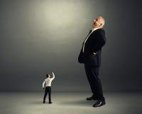 Uomo che mostra pugno al grande uomo d'affari Immagine Stock