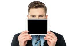 Uomo che nasconde il suo fronte con il dispositivo della compressa Fotografie Stock