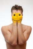 Uomo che nasconde il suo fronte nell'ambito della mascherina di sorriso immagini stock libere da diritti