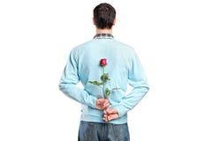 Uomo che nasconde un fiore dietro suo indietro fotografia stock