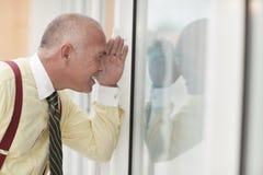 Uomo che osserva attraverso il vetro immagine stock