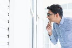 Uomo che osserva attraverso la finestra Fotografia Stock