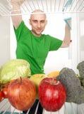 Uomo che osserva in frigorifero Fotografie Stock