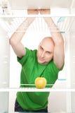 Uomo che osserva in frigorifero vuoto Immagine Stock