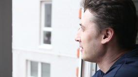 Uomo che osserva fuori la finestra video d archivio