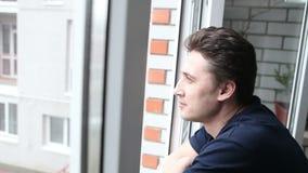 Uomo che osserva fuori la finestra stock footage