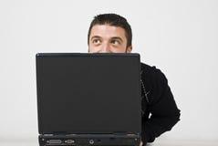 Uomo che osserva in su dietro il computer portatile Fotografie Stock Libere da Diritti