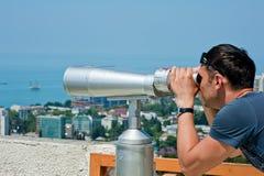 Uomo che osserva tramite il binocolo Fotografie Stock Libere da Diritti