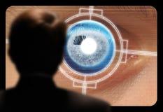 Uomo che osserva una ricerca retinica dell'occhio su un video monitor Fotografia Stock Libera da Diritti