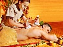 Uomo che ottiene i trattamenti di erbe di massaggio della palla. Immagini Stock
