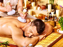 Uomo che ottiene i trattamenti di erbe di massaggio della palla. Immagine Stock Libera da Diritti