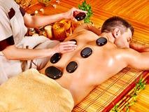 Uomo che ottiene massaggio di pietra di terapia. Fotografia Stock Libera da Diritti