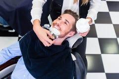 Uomo che ottiene rasatura della barba nel salone del barbiere immagine stock