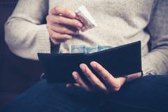 Uomo che ottiene soldi dal suo portafoglio Fotografie Stock
