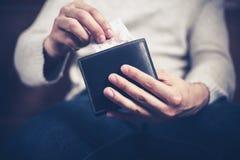 Uomo che ottiene soldi dal suo portafoglio Immagini Stock Libere da Diritti