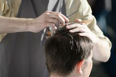 Uomo che ottiene taglio di capelli al negozio di barbiere Capelli di taglio del parrucchiere del cliente al salone Immagini Stock