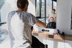 Uomo che ottiene taglio di capelli al negozio di barbiere Parrucchiere che disegna capelli del cliente al salone fotografia stock