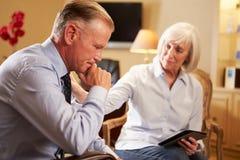 Uomo che parla con consulente femminile che usando la linguetta di Digital Immagine Stock Libera da Diritti