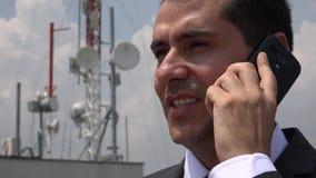 Uomo che parla sul telefono vicino alla torre cellulare