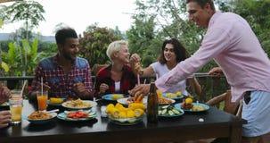 Uomo che passa alimento alla gente che si siede alla Tabella che mangia la giovane riunione del gruppo degli amici sul terrazzo d stock footage