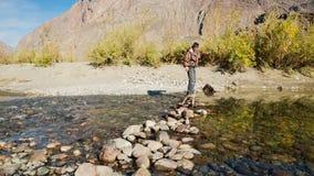 Uomo che passa attraverso il fiume della montagna stock footage