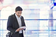 Uomo che per mezzo del computer della compressa alla stazione ferroviaria Fotografia Stock Libera da Diritti
