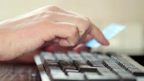 Uomo che per mezzo del computer per l'acquisto online con la carta di credito stock footage