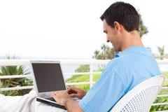 Uomo che per mezzo del computer portatile Immagini Stock Libere da Diritti