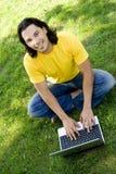 Uomo che per mezzo del computer portatile all'aperto Immagine Stock