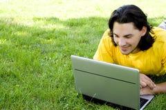 Uomo che per mezzo del computer portatile all'aperto Fotografie Stock Libere da Diritti