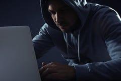 Uomo che per mezzo del computer portatile ATTIVIT? CRIMINALE fotografia stock