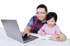 Uomo che per mezzo del computer portatile mentre aiuti il suo studio del bambino Immagine Stock