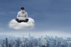 Uomo che per mezzo del computer portatile sopra la nuvola 1 Immagini Stock Libere da Diritti