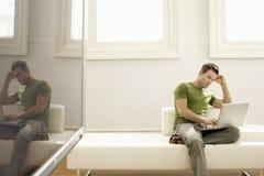 Uomo che per mezzo del computer portatile su Sofa In Modern Apartment immagine stock