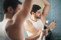 Uomo che per mezzo del deodorante di spruzzo sopra sotto le ascelle per il cattivo odore Fotografia Stock