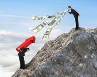 Uomo che per mezzo del megafono che spruzza fuori le banconote in dollari che urlano ad un altro Immagine Stock