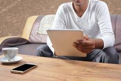 Uomo che per mezzo del pc della compressa con lo schermo mobile in bianco sulla tavola immagini stock