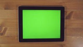 Uomo che per mezzo del PC della compressa con lo schermo verde video d archivio