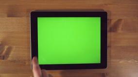 Uomo che per mezzo del PC della compressa con lo schermo verde archivi video