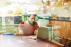 Uomo che per mezzo del suo computer portatile Immagini Stock Libere da Diritti