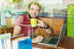 Uomo che per mezzo del suo computer portatile Immagini Stock