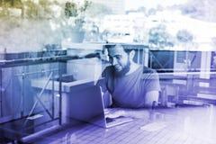 Uomo che per mezzo del suo computer portatile Fotografia Stock