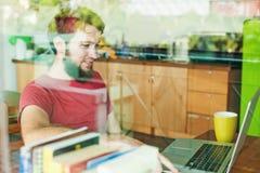 Uomo che per mezzo del suo computer portatile Immagine Stock Libera da Diritti