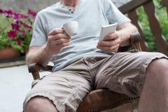 Uomo che per mezzo del suo smartphone e tenendo una tazza di caffè Immagini Stock Libere da Diritti
