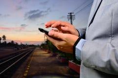 Uomo che per mezzo del suo telefono cellulare sulla piattaforma ferroviaria vuota Primo piano h Fotografia Stock Libera da Diritti